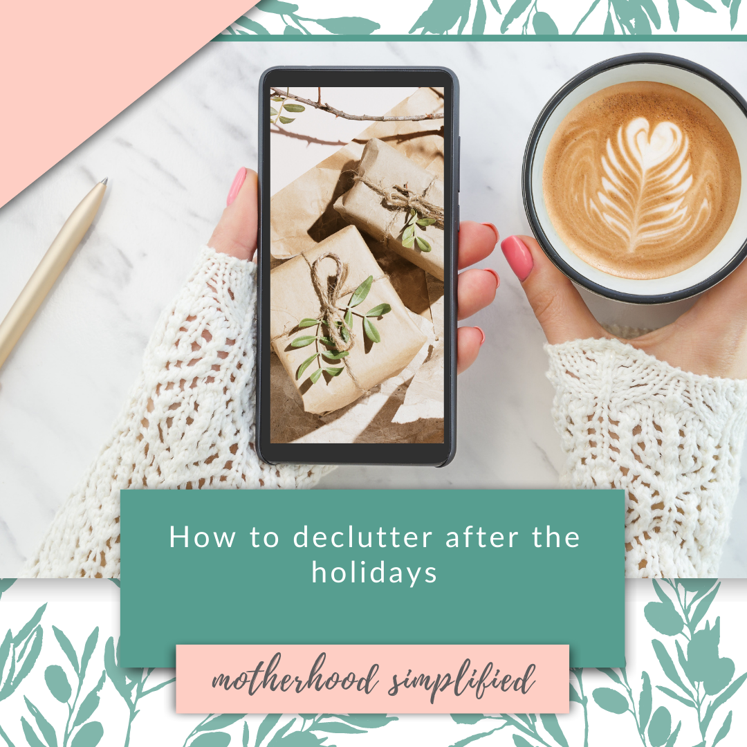 "This is a branded image. It has pink and green text with a hand holding a cup of coffee and smart phone. The image on the smart phone is some wrapped gifts, the text on the image says ""how to declutter after the holidays"" with the Motherhood Simplified logo below."