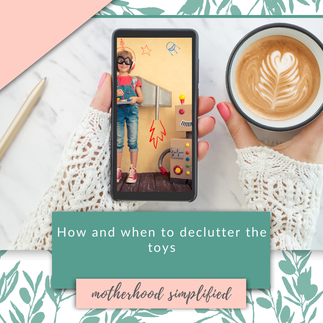 "This is a branded image with a pink and green background. There is a hang holding a smart phone and some coffee. The image on the smart phone is a child playing with a cardboard box robot. The text says "" how and when to declutter toys "" with the Motherhood Simplified logo below."